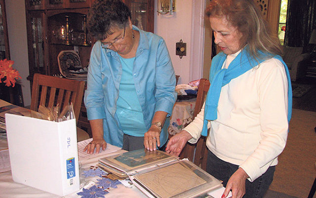 Sisters Treasure Cohen, left, and Rebecca Lubetkin look over some of the documents left by their parents.