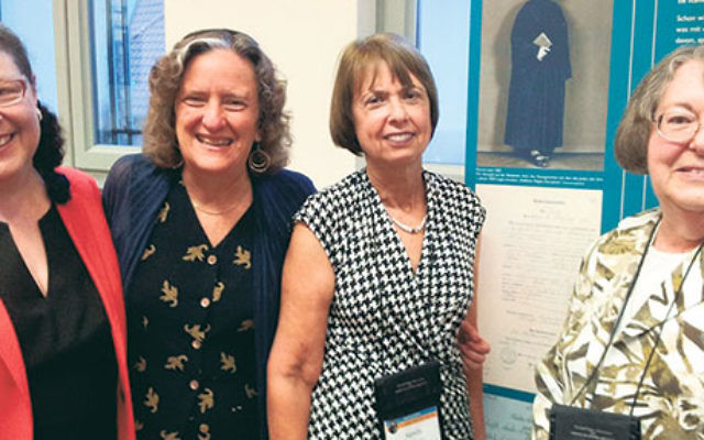 Rabbi Sally Priesand, right, with other pioneering rabbis, from left, Jacqueline Tabick, Amy Eilberg, and Sandy Eisenberg Sasso, with a photo of Rabbi Regina Jonas at Centrum Judaicum Archive in Berlin, July 22.