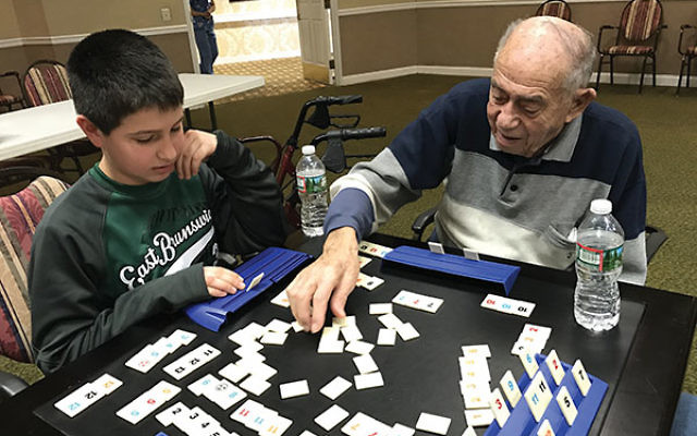 Reaching out across the age barrier to bring comfort, a youngster plays cards with a senior member of the congregation.