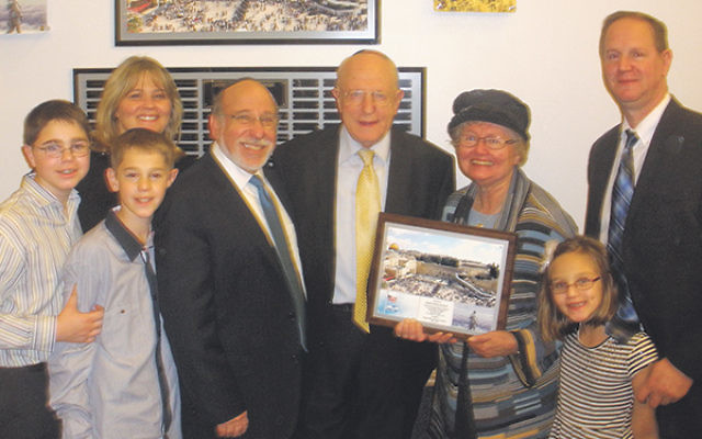 "Henry and Sheila Schanzer hold the plaque they were given to commemorate dedication of a ""wall of honor"" they sponsored for former RPRY students who have served or are serving in the IDF; with them are some of their children and grandchildren"