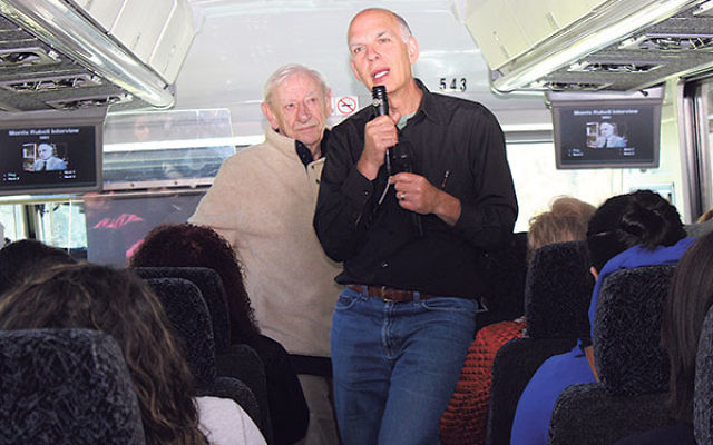 Survivor Fred Heyman, left, and Michael Rubell address the participants on the bus ride to Washington.