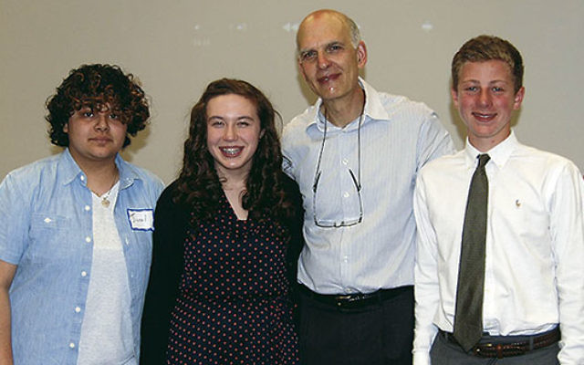 Michael Rubell, second from right, honors three students for their work on promoting Holocaust awareness, from left, Grace Gentle, Ella DeBode, and Harry Kern.