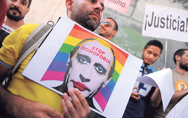 A man holds a sketch showing Russian President Vladimir Putin wearing lipstick during a protest against Russian anti-gay laws outside the Russian embassy in Madrid, Aug. 23, 2013.