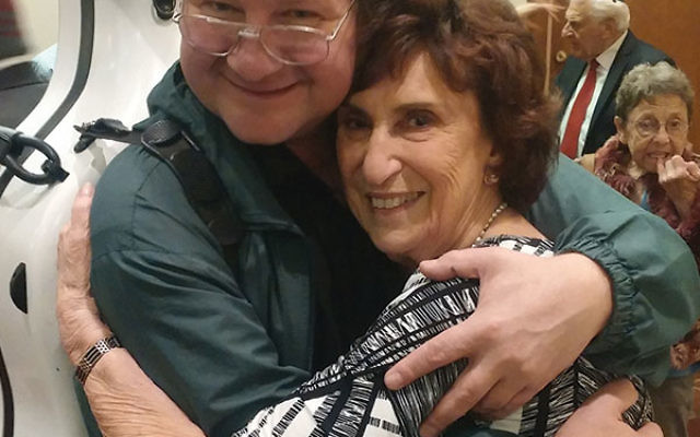 Oheb Shalom Congregation member Sheila Appel gets a thank-you hug from Andrey Tchekmazov, whose family she helped settle in South Orange.