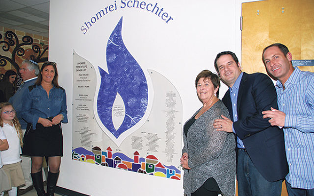 Susan Markowitz, left, SSDS art teacher and designer of the plaque seen here, joins, from left, Maxine Macnow, Peter Opatut, and Elan Levy of the SSDS board, as they present the Shomrei Schechter Wall of Honor.
