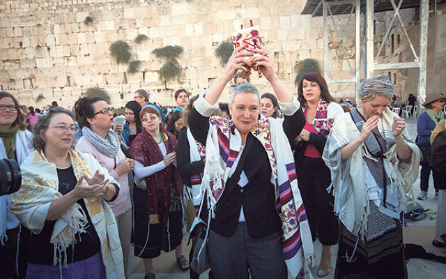 Lesley Sachs holds aloft a tiny Torah scroll during a Women of the Wall service at the Kotel.