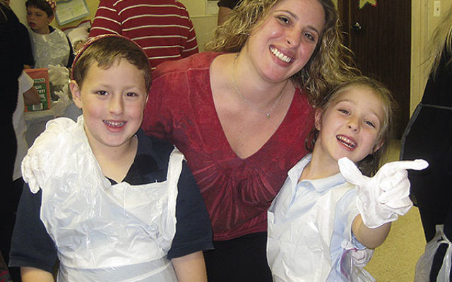 Shiri Arroyo and her children, Izzy and Maytal, former students at the Raritan Valley Solomon Schechter Day School, get into a family halla-baking event at their new school, SSDS of Greater Monmouth County.