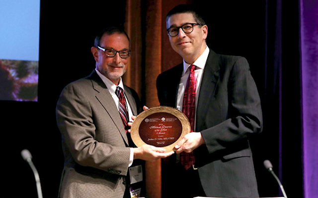 Dr. Paul Katz, chair of the AMDA Foundation, presents the 2017 Medical Director of the Year award to Dr. Joshua Schor at AMDA's annual conference in Phoenix.
