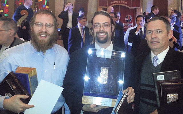 Yair Shahak, center, displays his first-place U.S. National Bible Contest for Adults trophy flanked by runners-up Alexander Heppenheimer, left, and Avrohom Horovitz.