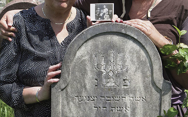 Lutwak, left, with her cousin Ronit Feingold in the cemetery in Sighet, standing at the grave of their great-grandmother Hinda Rivka, who died in 1920. They are holding a photo of their grandparents with their four children. Of all six, only Lutwak'