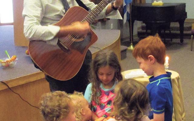 Rabbi Joel Simon plays Shabbat blessings on his guitar for kids from the Shir Ami preschool.