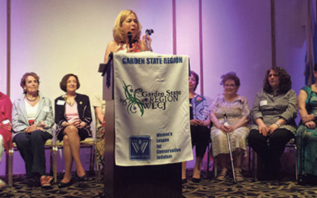 Ilene Rothman, surrounded by the evening's honorees, addresses the gathering.