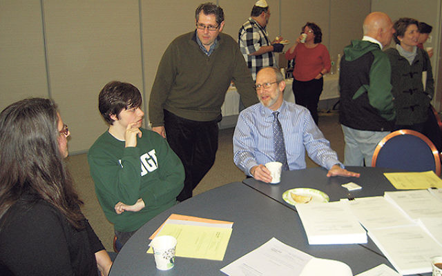 Rabbi John Schechter, seated, right, and Howard Stolzer, standing, led the discussion at Congregation B'nai Israel about a new Hebrew high school, open to students from across the region.