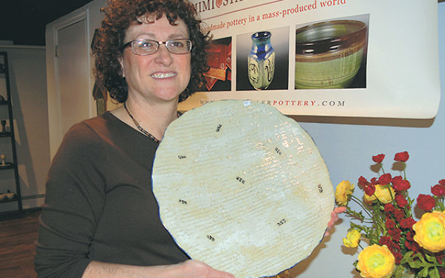 Hillside artist Mimi Stadler shows the matza plate she textured using actual matza.