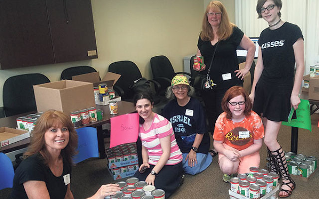 Volunteers, from left, Lisa Wax, Shayna and Maryanne Mandelbaum, and Shari, Molly, and Samantha Bates help pack the bounty collected during the Supermarket Sweep.