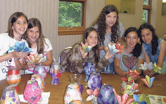 Youngsters at the TLC program of Camp Keshet at Young Israel of East Brunswick, with decorated vases and paper flowers to be given to seniors.