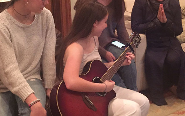 Alma Schneider's daughter plays the guitar in front of friends and a Syrian guest on Thanksgiving.