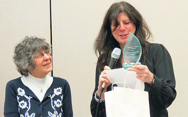 Melanie Roth Gorelick receives a trophy for her work with the NJ Coalition Against Human Trafficking; it was presented by Susan Neigher, left.
