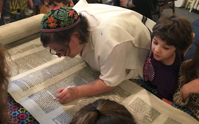 Soferet Linda Coppleson shows religious school students how she repairs a letter.