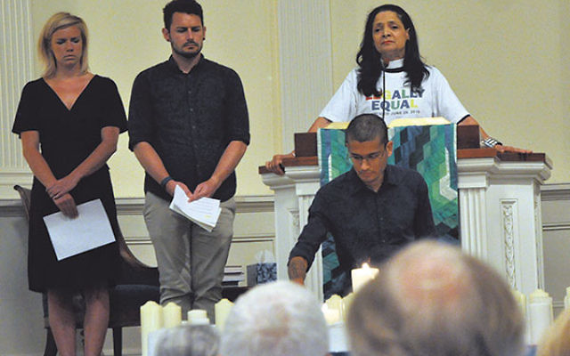 The Rev. Karen Hernandez-Granzen of Westminster Presbyterian Church in Trenton and members of the Princeton Theological Seminary student group BGLASS (Bisexual, Gay, Lesbian, and Straight Supporters) recite the names of Orlando victims and light candles i