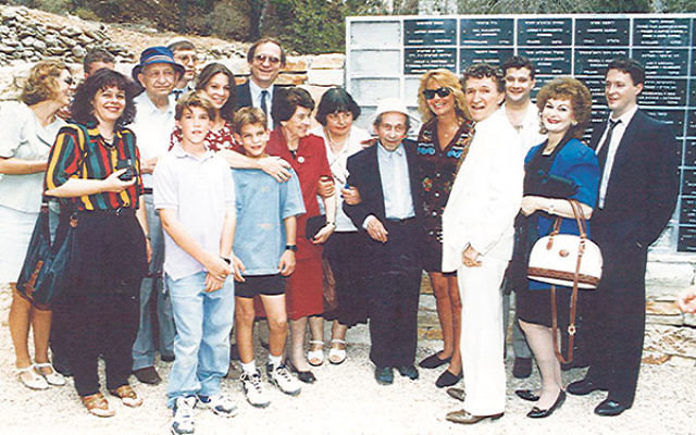 Michael Zeiger, front row, third from right, and other family members with Anton Suchinski, center, in Yad Vashem's Garden of the Righteous, the Wall of Honor, which bears his name, behind them, 1992.