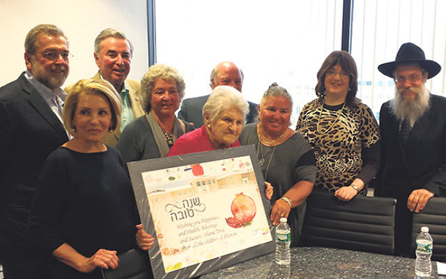 Clara Kramer, center, holds the New Year's greeting presented to her by Rabbi Shlomo Wilhelm and his wife, Esther, right, in gratitude for her support of their Jewish community center in Zhitomir. With them are, from left, Eli Kramer, Toby Goldberge