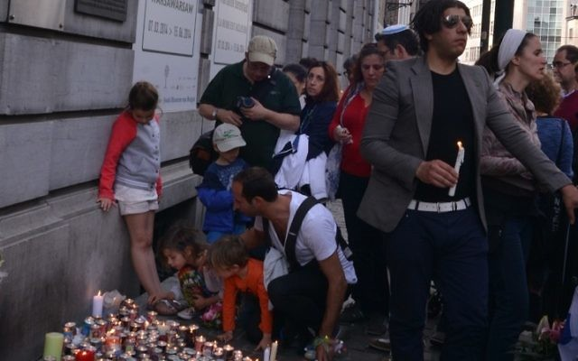Adults and children participating in a silent vigil outside the Jewish Museum of Belgium in Brussels for the four victims of a shooting there by an unidentified gunman, May 25, 2014. (Cnaan Liphshiz)