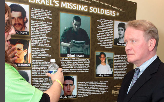Rep. Leonard Lance (R-NJ Dist. 7) talks with Adina Abramov at last December's Super Sunday in Scotch Plains about the poster she created showing Israel's missing soldiers. Photo by Elaine Durbach