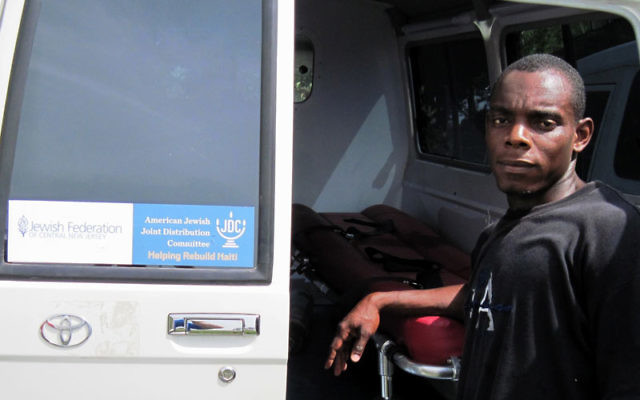 A Haitian worker checks out the ambulance purchased with funds raised by the Jewish Federation of Central New Jersey and delivered last month. Photo courtesy American Jewish Joint Distribution Committee