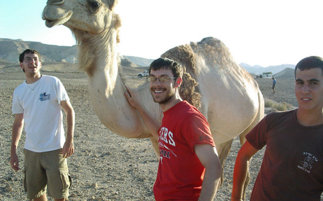 Yossi Mason, center, and fellow counselors meet one of the denizens of the Negev while on a Kefiada trip to Israel.