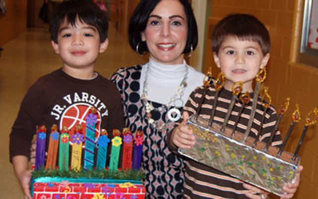 JCC preschool teacher Mindy Katz presents two of her artists, Noah Rotondo, left, with his craft stick menora, and Hayden Cear with his menora, made of twigs and pipe cleaners.