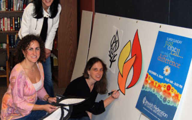 Super Sunday co-vice-chair Lisa Israel, standing, works with, from left, Robin Plattman, and Liz Isser on the display board to be used at the annual fund-raiser on Dec. 6.