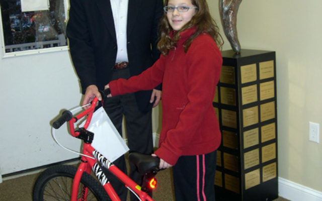 Lillia Shub presents the bicycle she won in a shul raffle to JFS executive director Tom Beck, to be given to a needy child. Photo courtesy of JFS