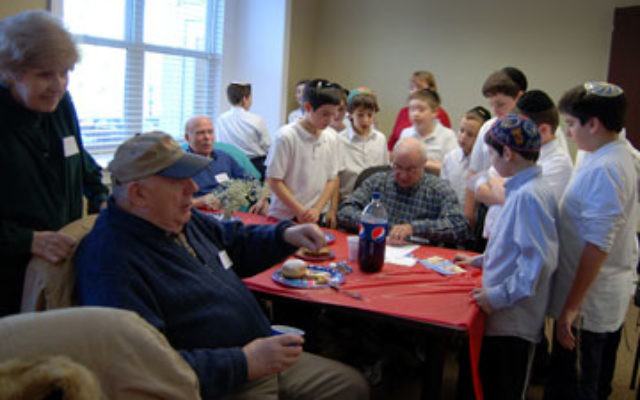 Boys from the JEC, who came to sing for seniors at a JFS Hanukka party, gather around Dave Lefkovic as he makes them paper airplanes. Looking on are Shirley and Moshe Rosenthal.