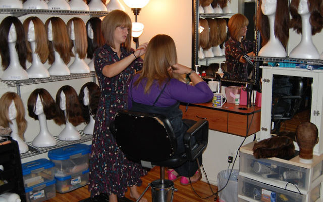 Wig expert Naomi Surtees styles a client's wig in her home salon in Hillside. Photos by Elaine Durbach
