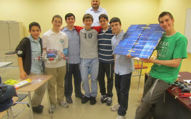 The JEC students chosen to take place in the final round of the international Gildor invention competition in Israel are, from left, Micah Lebowitz, Ethan Lerner, Noam Shachak, Pinchas Teitz, Tzvi Vogel, Rafi Taub, and Shimon Niren. Behind them is their c