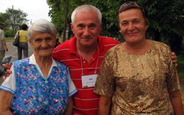 Bill Gottdenker with two local women in Bolechow. The woman on the right helped members of the Bolechow Jewish Heritage Society clean up the town's Jewish cemetery the next day.