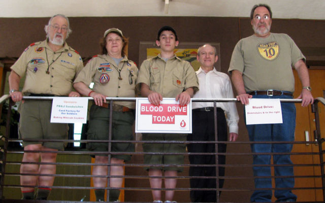 Micah Lubow, center, observes the Eagle Scout project/Mitzva Day activities he organized at Temple Beth-El Mekor Chayim, with, from left, Troop 118 scoutmaster Mike Schatzberg; assistant scoutmaster Rabbi Lisa Vernon; Micah's father, Rabbi Akiba L