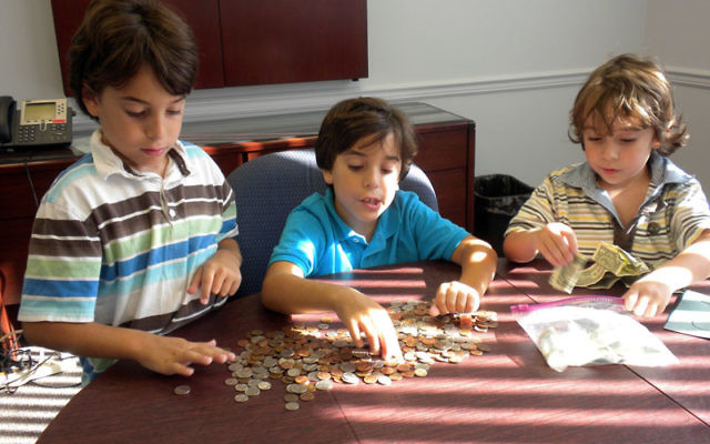 Lee Brewster, center, counts the money he collected for the poor, helped by his brothers, Ryan, left, and William, at the Central federation.