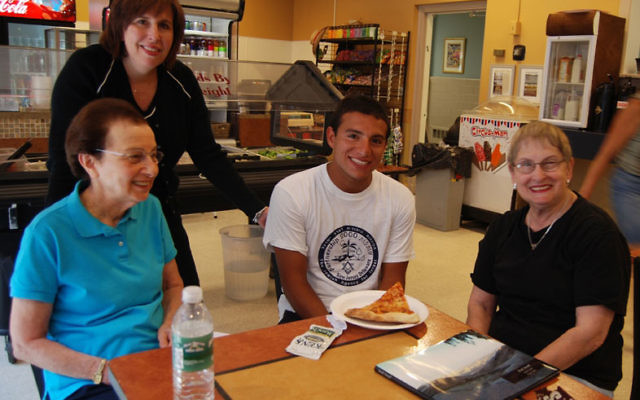 Federation executive Amy Cooper, rear, joins Living Bridge volunteers Clair Bisgay, left, and Marjorie Cohen, in telling JCC counselor Danny Nieto last year about their experience working in Israel. Photo by Elaine Durbach