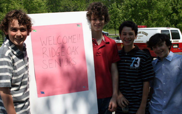 Sixth-graders, from left, Max Berg, Alex Simon, Jared Weinerman, and Drew Berger hold up a sign to greet Ridge Oak seniors at a luncheon hosted by their class at Congregation B'nai Israel in Basking Ridge. Photos courtesy Congregation B'nai