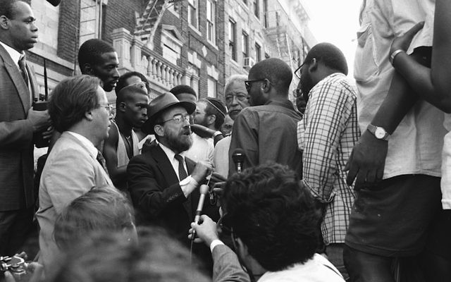 New York City Mayor David Dinkins, fourth from right, looking on while a Hasidic Jew and a black man argue during riots in Crown Heights, Brooklyn, in 1991.