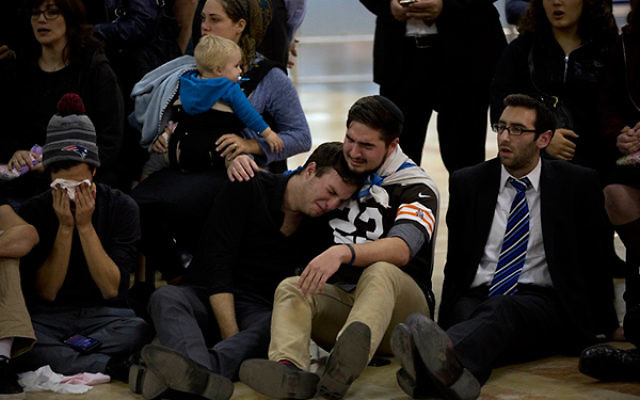 Friends of Ezra Schwartz grieving for the American terror victim at a service at Ben Gurion Airport in Israel before the body was repatriated to Boston for his funeral the following day, Nov. 21, 2015. (AP Images/Oded Balilty)