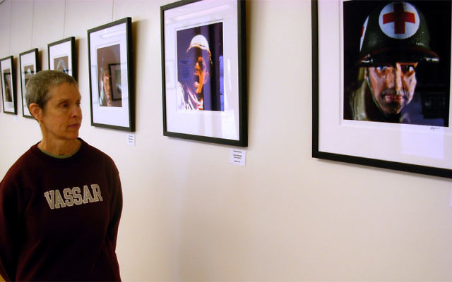 """Lisa Suss, visual arts manager for JCC MetroWest's Gaelen Center for the Arts, views Howard Heyman's """"Portraits: Toy Soldiers,"""" part of the """"Photographer/Provocateur"""" exhibit at Gaelen Gallery East at the Cooperman JCC."""