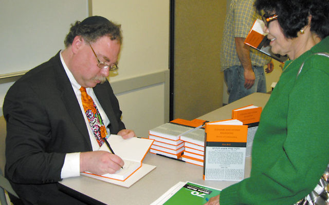 Rabbi Alan Brill signs a copy of his new book, Judaism and Other Religions: Models of Understanding, at Seton Hall University March 21. Photo by Robert Wiener