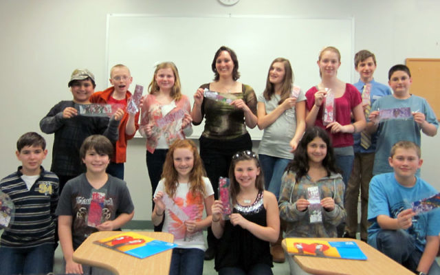 Jackie Frankel, center, the Jaffa Institute's youth fund-raising coordinator, and the Monmouth Reform Temple's sixth-grade class proudly display the bookmarks they created for their Mother's Day fund-raiser, including, from left, front r