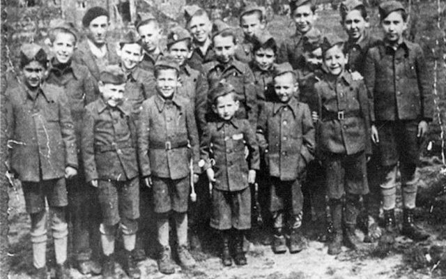 """Abe Chapnick, last row, second from right, and Robbie Waisman, third from right, pose with fellow child survivors from Buchenwald sent for """"rehabilitation"""" in France, in clothes made for them from former SS uniforms."""