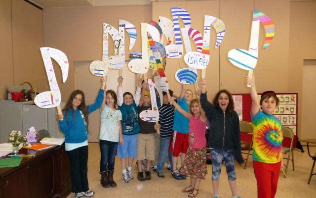 "Students at Temple Beth Ahm in Aberdeen display the musical notes they created to reflect the theme ""Singing Derech Eretz Israel"" for their contingent in the Celebrate Israel Parade."