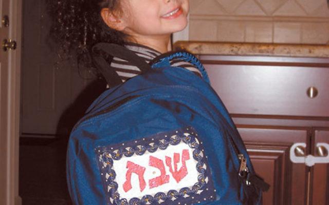 Alexa Tanzer, a member of the Solomon Schechter pre-kindergarten class, arrives home with the Shabbat Backpack.