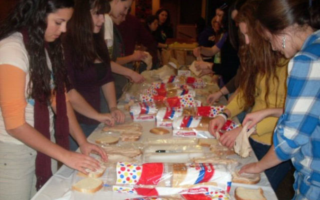 Teens from Temple Beth Miriam youth group assemble sandwiches the evening of Jan. 23 before their Midnight Run to Manhattan to distribute food, clothing, and toiletries to the homeless.